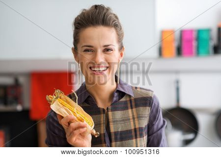 Closeup Of Smiling Woman Holding Up A Corn Cob With Its Husk