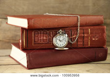 Pocket clock and vintage books, on rustic wooden background