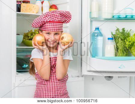 little girl cook holding big onions close to cheeks near opened fridge