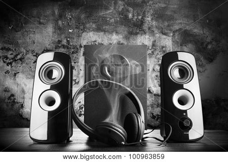 Modern black sound speakers and headphones smoking from overload