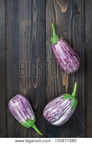 Purple eggplant onion beans garlic and basil leaves from above on the old wooden board with free tex
