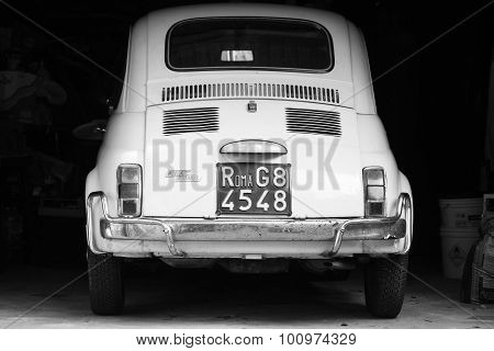 Old White Fiat 500 L Car Stands In Dark Garage