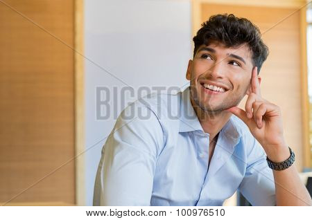 Closeup shot of young man smiling and looking up. Handsome young man smiling and looking away. Portrait of man thinking and imaging. Contemplative man with shirt thinking and smiling about the future.