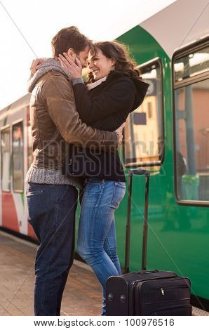 Happy couple embracing on railway station platform. Farewell at the train station