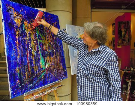 Modern artist drips paint from a plastic bottle onto his canvas