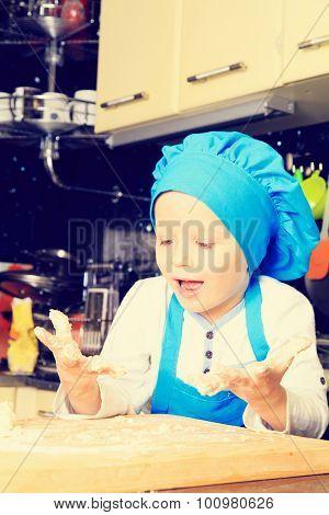 little boy kneading dough in kitchen