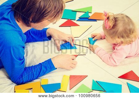 teacher and child playing with geometric shapes