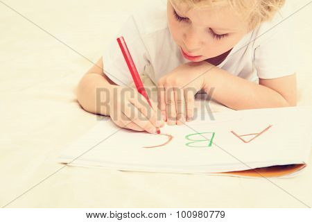 little boy learning to write letters