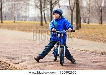 little boy on running bike in autumn