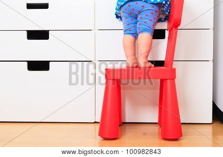 kids safety concept- little girl climb on chair