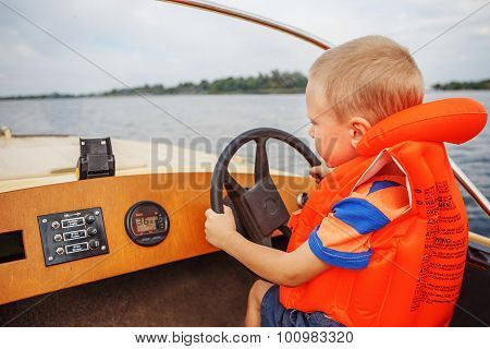 Little Boy Driving A Motor Boat Firmly Holding The Steering Wheel