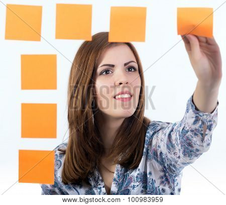 Young lady attaches sticker to the board
