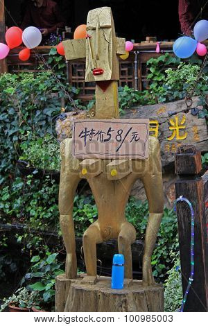 interesting wooden statue of naked woman on the street