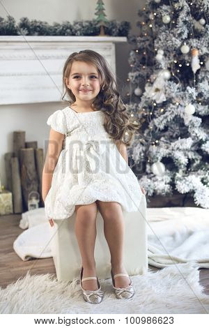 5 years old little girl dressed in beautiful fashion white flower dress posing near Christmas tree