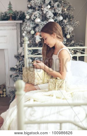 Preteen child girl wake up in her bed near decorated Christmas tree in beautiful hotel room in the holiday morning, opening presents