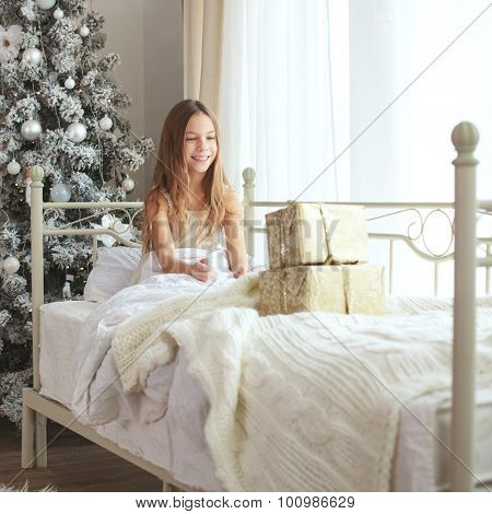 Preteen child girl wake up in her bed near decorated Christmas tree in beautiful hotel room in the holiday morning, surprised with presents