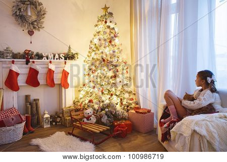 Child girl sitting near decorated Christmas tree and fireplace in comfortable chair at home