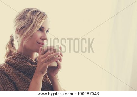 Woman wearing warm knitted sweater is drinking cup of hot tea or coffee near window in autumn morning sunlight, photo warm toned