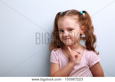 Cunning Thinking Small Kid Girl With Finger Near Face On Blue Background