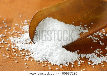 Coarse grained salt on a wooden scoop