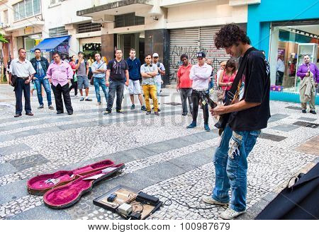 SAO PAULO, BRAZIL - APRIL 17, 2015: An unidentified musician playing guitar  in main street of Sao  Paulo on April 17, 2015, Brazil.