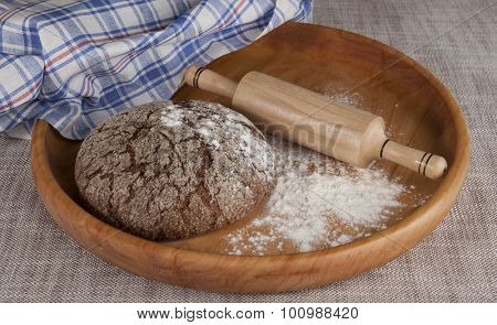 Fresh homemade bread made from durum wheat, rye, on a wooden tray with  a rolling pin. Composition on a beautiful tablecloths canvas. Photos for magazines about cooking, confectionery, cooking.