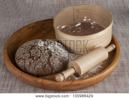 Fresh homemade bread made from durum wheat, rye, on a wooden tray with a sieve for flour and a rolling pin. Composition on a beautiful tablecloth.