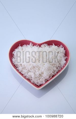 Top view of a heart shaped container filled with shredded coconut on a white background.