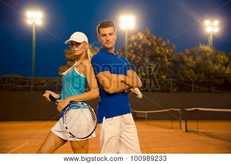 Portrait of a beautiful couple standing at tennis court outdoors