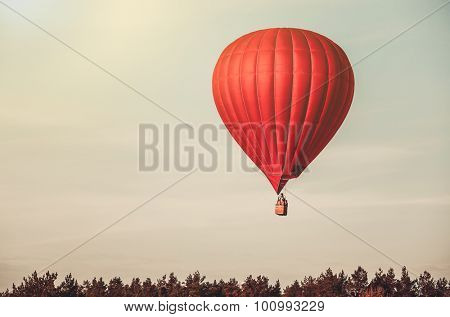 Red balloon in the  sky with forest in the down