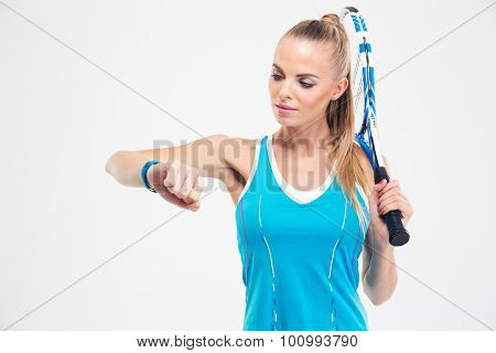 Portrait of a beautiful female tennis player looking on fitness tracker isolated on a white background