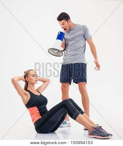 Concept photo of a trainer screaming through loudspeaker on a  woman to doing exercises isolated on a white background
