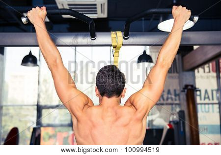 Back view portrait of a man tightening at gym