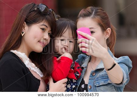 MANDALAY,MYANMAR,JANUARY 16, 2015 : Korean women are shooting a selfie (self portrait) with a funny bored little girl in a street of Mandalay, Myanmar (Burma).