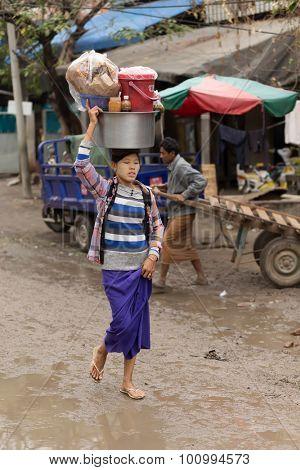 AMARAPURA, MYANMAR, JANUARY 17, 2015: A woman is carrying a bag on her head, walking in the dirty street of the Zegyo market, in Mandalay, Myanmar (Burma).