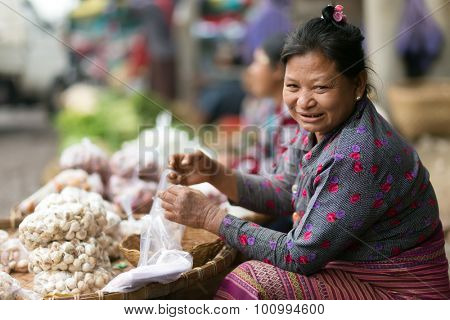MANDALAY,MYANMAR,JANUARY 17, 2015 : Portrait of a woman selling onions in the central street market of Zegyo, in Mandalay, Myanmar (Burma).