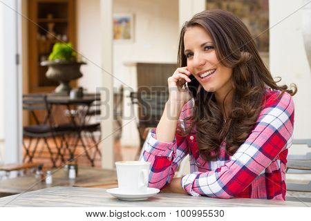 Beautiful smiling woman talking on cell phone at cafe