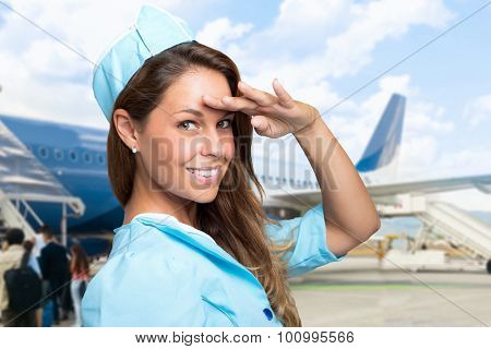 Portrait of a smiling stewardess in front of a plane