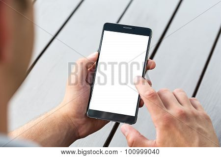 Man Holding Smart Mobile Phone On Wooden Table