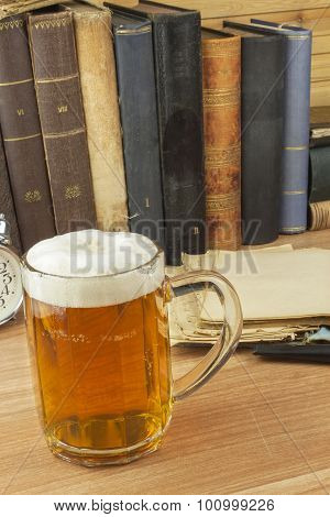 Cool glass of beer on the table. Relax with a good book with a glass of cold beer.