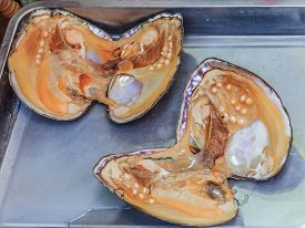 stock photo of pearl-oyster  - Pearl oyster shell with pearls inside for sale at the market in China - JPG