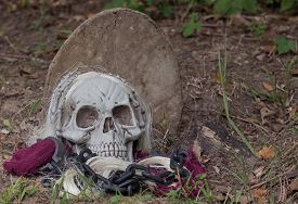 picture of tombstone  - Grim reaper halloween prop on the ground with tombstone - JPG