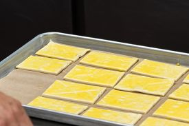 pic of pastry chef  - close up of a chefs hands placing prepared puff pastry on a tray for baking - JPG