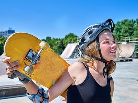 picture of skateboard  - Teen skateboarding his skateboard and hold on her back outdoor - JPG