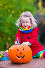 stock photo of carving  - Little girl and boy carving pumpkin at Halloween - JPG