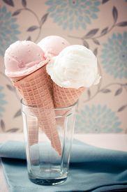 stock photo of gelato  - Italian gelato scoops on sugar cones with soft nostalgic warm retro tone - JPG