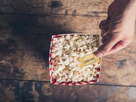 picture of matinee  - Cinema concept of hand holding movie ticket above a box of popcorn - JPG