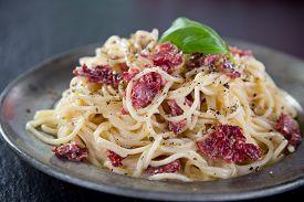 stock photo of carbonara  - Italian pasta carbonara with tomato and basil - JPG