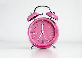 stock photo of analog clock  - Pink analog retro twin bell alarm clock - JPG