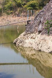 image of suspension  - above the water between two rocks hangs a suspension bridge - JPG